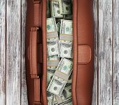 pic of billion  - suitcase full of dollars on a wooden background - JPG