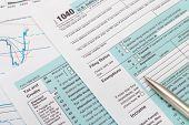 stock photo of cpa  - US 1040 Tax Form and silver ball pen - JPG