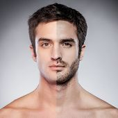 picture of macho man  - Handsome young man with half shaved face looking at camera while standing against grey background - JPG