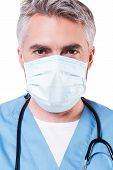 stock photo of only mature adults  - Mature grey hair doctor in surgical mask looking at camera while standing isolated on white - JPG