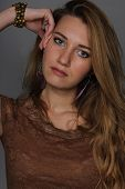 pic of neutral  - studio portrait of the thoughtful young girl with a long fair hair of 25 years in a brown blouse on a neutral background the hand at the level of eyes - JPG