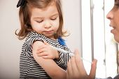 picture of flu shot  - Closeup of a cute little girl getting a flu shot at a doctor - JPG