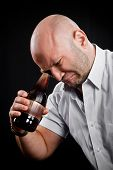 stock photo of hillbilly  - man very emotionally looks at the bottom of the bottle with beer - JPG