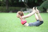 image of dhanurasana  - Yoga dhanurasana bow pose by asian woman on lawn - JPG