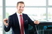 stock photo of showrooms  - Seller or car salesman in car dealership with key presenting his new and used cars in the showroom - JPG