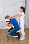 stock photo of physiotherapist  - Female Physiotherapist Giving Shoulder Massage To Man On Massage Chair - JPG