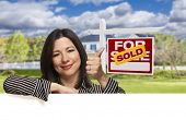 stock photo of real  - Pretty Hispanic Woman Leaning on White with Thumbs Up in Front of Beautiful House and Sold For Sale Real Estate Sign - JPG