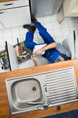 picture of sink  - Male Plumber Examining Sink In Kitchen Holding Clipboard - JPG