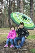 pic of little sister  - Spring in the woods sitting on a stump a little boy with curly little sister under an umbrella - JPG