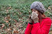 image of overcoats  - Young woman suffering from a cold or flu blowing her nose on a white paper handkerchief on a forest wearing a red overcoat - JPG