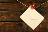 picture of revelation  - Love letter hanging on rope on rustic wooden background - JPG