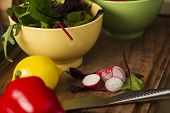 picture of rocket salad  - Bowl of fresh herbs with rocket and baby spinach and assorted salad ingredients including a lemon red bell pepper and radish on a kitchen counter waiting to be prepared for dinner - JPG