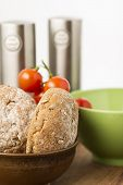 stock photo of baps  - Freshly baked brown wholegrain bread rolls in a bowl in the kitchen with a bunch of cherry tomatoes ready to prepare a healthy sandwich snack - JPG