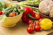 foto of spears  - Delicious fresh vegetables for dinner standing ready to prepare on a kitchen counter with ripe cherry tomatoes red bell pepper lemon asparagus spears baby spinach and brown bread rolls - JPG