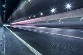 stock photo of speeding car  - speeding lights of cars in city at night - JPG