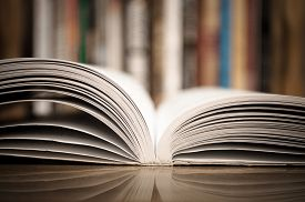 picture of reflections  - Open book on the wooden table with defocused books in the background - JPG