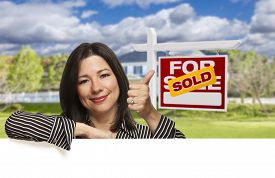 stock photo of sign-boards  - Pretty Hispanic Woman Leaning on White with Thumbs Up in Front of Beautiful House and Sold For Sale Real Estate Sign - JPG