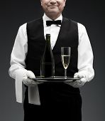 stock photo of flute  - butler with champagne flute and bottle on tray - JPG