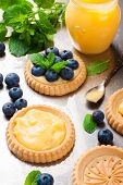 foto of curd  - Process of making shortbread tartlet filled with lime curd and blueberries on old vintage metal background - JPG