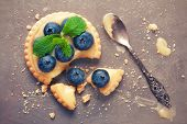 stock photo of curd  - Shortbread home made broken tartlet filled with lime curd and blueberries on old vintage metal background - JPG