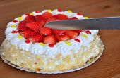picture of hand cut  - Hand is cutting cream cake with fresh strawberries on the plate on the wooden table - JPG