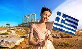 stock photo of poseidon  - Woman holding Greek flag on ancient ruins of Poseidon temple background in Sounion - JPG