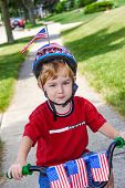 foto of parade  - Boy riding his bicycle in a 4th of July neighborhood parade - JPG