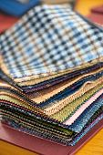 image of tailoring  - Fabric samples or swatches of various textiles for garment making in a tailors shop or seamstress showing an assortment of colors and textures - JPG