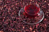 foto of hibiscus  - Cup of hibiscus tea in a heap of dried petals of hibiscus - JPG