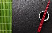 pic of soy sauce  - Japanese sushi chopsticks over soy sauce bowl on black stone background - JPG