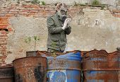 foto of nuclear disaster  - Man with gas mask and green military clothes explores dead bird after chemical disaster - JPG