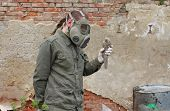 stock photo of nuclear disaster  - Man with gas mask and green military clothes explores dead bird after chemical disaster - JPG