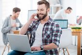 image of people talking phone  - Happy young man working on laptop and talking on the mobile phone while two people working in the background - JPG