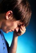 stock photo of sorrow  - Sorrowful Young Man in the Dark Room - JPG