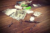 picture of drug dealer  - Drugs money needles and syringes on a wooden background - JPG