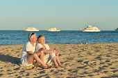 picture of couple sitting beach  - Happy mature couple sitting on a beach - JPG