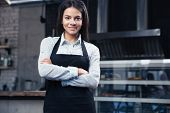 picture of apron  - Happy charming female waiter in apron standing with arms folded in restaurant and looking at camera - JPG