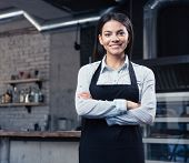 stock photo of apron  - Happy cute female waiter in apron standing with arms folded in cafe - JPG