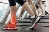 pic of treadmill  - Digital composite of Highlighted ankle of woman on treadmill - JPG