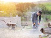 pic of bricklayer  - Bricklayer cutting a brick with circular saw - JPG