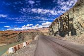 foto of jammu kashmir  - A concrete road towards beautiful rocky mountains and snow peaks of Himalaya Leh Ladakh Jammu and Kashmir India - JPG