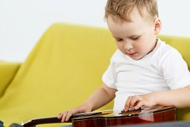 foto of string instrument  - Little child sitting on couch and examine ukulele guitar - JPG