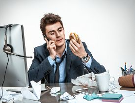 stock photo of not talking  - Slacker man talking on the phone while eating at work  - JPG