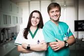 Постер, плакат: Young experienced doctors dentists standing along with nurse assistant