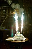 image of birthday-cake  - Cake with candle and flame on dark background - JPG