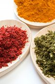 stock photo of hyssop  - Various spices in different colors on wooden spoons