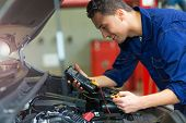Auto mechanic checking car battery voltage  poster