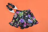 floral skirt with white shoes isolated-orange background