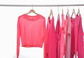 red sweater, pink shirt with colorful clothes on a hanger –on white background