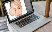retouch, technology and design concept - laptop computer with woman face image in graphics editor on poster